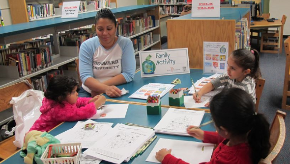 A group of preschoolers participate in coloring activities during a Family Fun Fest at the Main Library.