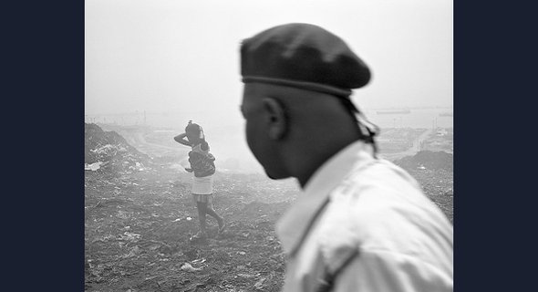 Conflict between Luanda's population and its governing elites forms an undercurrent to this photograph of a young woman carrying a baby across litter-strewn ground, observed by a man wearing a military beret.