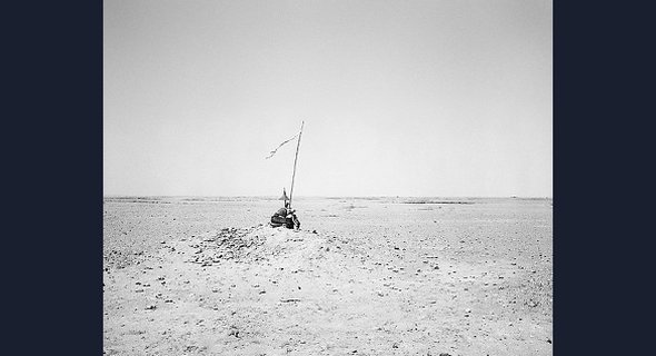 UNIDENTIFIED MEMORIAL IN THE DESERT, SOUTH OF NAMIBE: An assemblage of objects perches on a stony outcrop, surrounded by desert. The long pole protruding from the pile is topped with a ragged banner, announcing the presence of this unusual memorial.